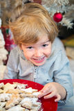Ragazzino sveglio che mangia i biscotti sul Natale Fotografia Stock Libera da Diritti