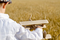 Ragazzino sveglio che pilota un aereo del giocattolo in un wheatfield Fotografia Stock