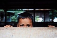 ragazzino sveglio che si nasconde dietro una parete che alza il suo verticalmente capo appena sopra fotografia stock