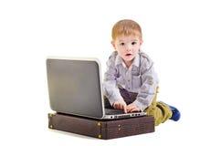 Ragazzino sveglio che si siede con un computer portatile Fotografie Stock
