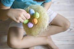 Ragazzino sveglio che tiene un nido con le uova di Pasqua colorate a casa sul giorno di Pasqua Celebrazione della Pasqua alla mol Fotografia Stock