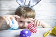 Ragazzino sveglio che tiene un nido con le uova di Pasqua colorate a casa sul giorno di Pasqua Celebrazione della Pasqua alla mol Fotografia Stock Libera da Diritti