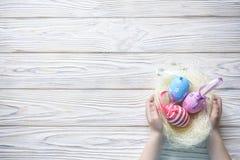 Ragazzino sveglio che tiene un nido con le uova di Pasqua colorate a casa sul giorno di Pasqua Celebrazione della Pasqua alla mol Immagini Stock