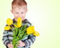 Ragazzino sveglio con i tulipani gialli Fotografia Stock