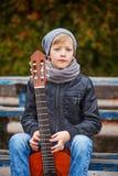 Ragazzino sveglio con la chitarra nel giorno di autunno È vestito in un bl fotografia stock libera da diritti