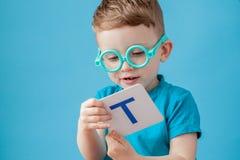 Ragazzino sveglio con la lettera su fondo Il bambino impara le lettere Alfabeto fotografia stock
