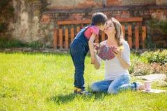 Ragazzino sveglio, dare presente alla sua mamma per il giorno di madri Fotografia Stock