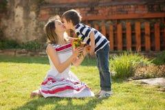 Ragazzino sveglio, dare presente alla sua mamma per il giorno di madri Fotografie Stock Libere da Diritti