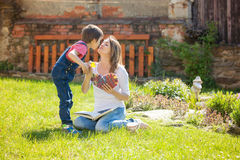Ragazzino sveglio, dare presente alla sua mamma per il giorno di madri in Th Fotografia Stock