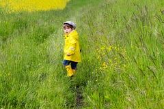 Ragazzino sveglio in impermeabile giallo, stivali di gomma e cappuccio camminante nel prato con erba verde che guarda indietro immagini stock