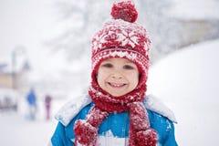 Ragazzino sveglio nel vestito blu di inverno, giocare all'aperto nella neve Fotografia Stock