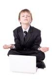 Ragazzino sveglio in vestito che si siede nella posa di yoga con il lapto Immagini Stock Libere da Diritti