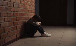 Ragazzino triste che si siede sul pavimento vicino al muro di mattoni fotografia stock