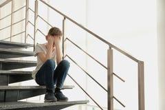 Ragazzino triste che si siede sulle scale all'interno fotografia stock libera da diritti