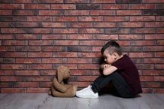 Ragazzino triste con il giocattolo che si siede sul pavimento vicino al muro di mattoni immagini stock libere da diritti