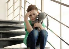 Ragazzino triste con il giocattolo che si siede sulle scale fotografie stock libere da diritti
