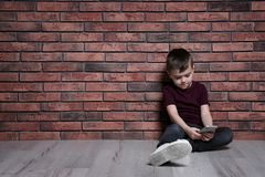 Ragazzino triste con il telefono cellulare che si siede sul pavimento Spazio per testo fotografie stock libere da diritti