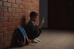 Ragazzino triste con il telefono cellulare che si siede sul pavimento vicino alla parete all'interno immagini stock libere da diritti