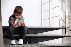 Ragazzino triste con il telefono cellulare che si siede sulle scale immagine stock libera da diritti
