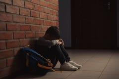 Ragazzino triste con lo zaino che si siede sul pavimento vicino al muro di mattoni immagini stock libere da diritti