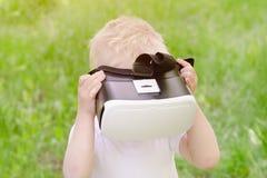 Ragazzino in un casco di realtà virtuale su un fondo di verde Immagini Stock Libere da Diritti