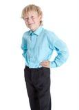 Ragazzo abbastanza biondo che porta camicia blu che esamina macchina fotografica, fondo bianco isolato Fotografia Stock