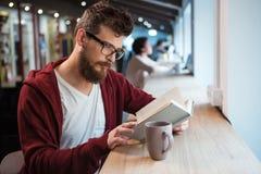 Ragazzo abile in libro di lettura di vetro che si siede allo scrittorio Immagine Stock