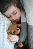 Ragazzo addormentato con il giocattolo dell'orso di orsacchiotto Immagini Stock