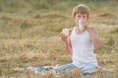 Ragazzo adolescente dell'agricoltore che assaggia latte e pane freschi Immagini Stock Libere da Diritti