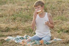 Ragazzo adolescente dell'agricoltore che mangia pane bianco fresco Fotografie Stock