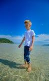 Ragazzo adorabile alla spiaggia tropicale Maglietta bianca, pantaloni scuri ed occhiali da sole A piedi nudi sulla sabbia bianca Fotografia Stock Libera da Diritti