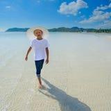 Ragazzo adorabile alla spiaggia tropicale Maglietta bianca, pantaloni scuri ed occhiali da sole A piedi nudi sulla sabbia bianca Immagini Stock Libere da Diritti