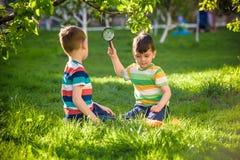 Ragazzo adorabile del bambino che fa fuoco sulla carta con un ou della lente d'ingrandimento Fotografie Stock