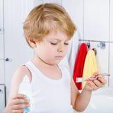 Ragazzo adorabile del bambino che pulisce i suoi denti, all'interno Immagini Stock
