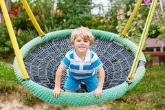 Ragazzo adorabile del bambino divertendosi oscillazione a catena su playgroun all'aperto Fotografia Stock