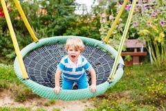 Ragazzo adorabile del bambino divertendosi oscillazione a catena su playgroun all'aperto Immagine Stock