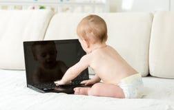 Ragazzo adorabile del bambino in pannolini che si siedono sul sofà e sul messaggio di battitura a macchina sulla tastiera del com Fotografie Stock Libere da Diritti