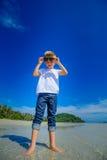 Ragazzo adorabile divertendosi sulla spiaggia tropicale Maglietta bianca, pantaloni scuri ed occhiali da sole A piedi nudi sulla  Fotografie Stock Libere da Diritti