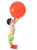 Ragazzo adorabile pronto in all'attrezzo di nuotata con la sfera arancione gigante sopra W Immagine Stock Libera da Diritti
