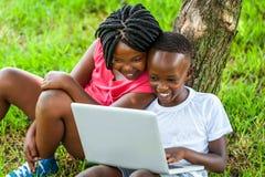 Ragazzo africano e ragazza che giocano sul computer portatile Fotografia Stock Libera da Diritti