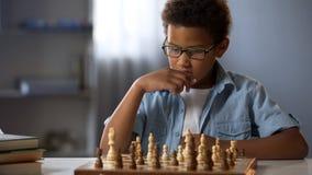 Ragazzo afroamericano che pensa logicamente fuori strategia a giocare scacchi, hobby fotografia stock