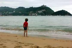 Ragazzo alla spiaggia che esamina l'acqua in tempo piovoso fotografie stock libere da diritti