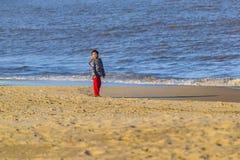 Ragazzo alla spiaggia alla stagione invernale Fotografia Stock