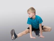 Ragazzo allegro che allunga la sua gamba Fotografie Stock