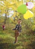 Ragazzo allegro con i palloni in autunno Fotografia Stock