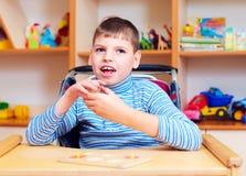 Ragazzo allegro con l'inabilità al centro di riabilitazione per i bambini con i bisogni speciali, risolvente puzzle logico Immagine Stock Libera da Diritti