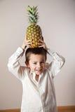Ragazzo allegro con un ananas sulla sua testa Fotografia Stock Libera da Diritti