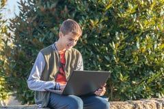 Ragazzo allegro dell'adolescente con il computer portatile ed i manuali che fanno compito e che preparano per un esame nel parco immagini stock libere da diritti