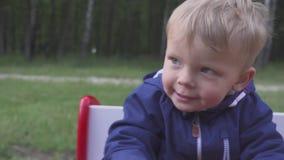 Ragazzo allegro di due anni che gioca su un'oscillazione dell'automobile del giocattolo portrite video d archivio