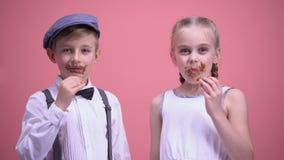 Ragazzo allegro e ragazza che sorridono e che mangiano le caramelle di cioccolato, celebranti festa stock footage